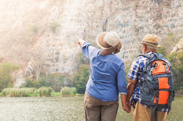 Elderly asian couples trekking high mountain enjoy life after retirement. elder community concept
