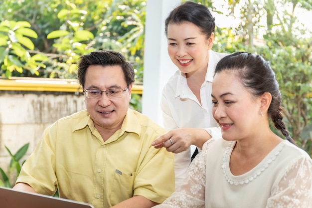 Elderly asian friends looking at laptop display in nursing home.