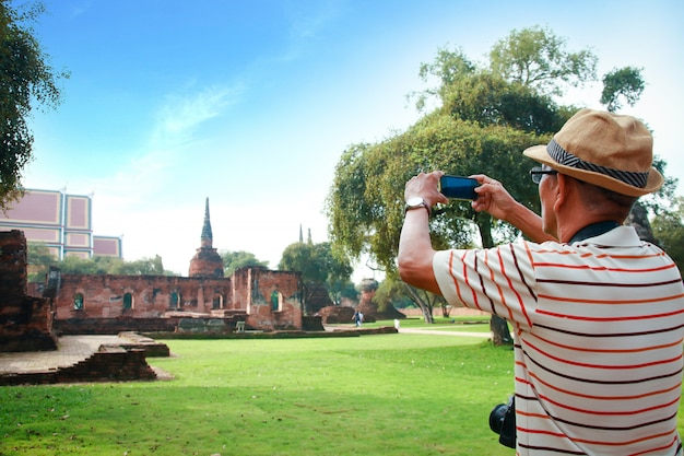 An elderly asian man holding a camera at an archaeological site in thailand