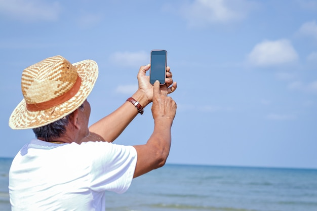 An elderly asian man holding a phone to take pictures in the sea