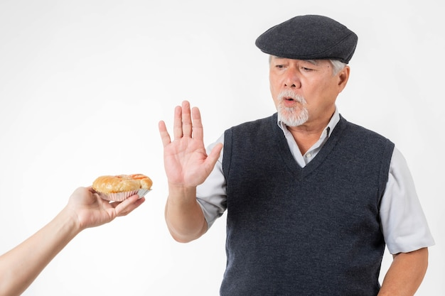 The elderly asian man raised his hand and refused to accept the pizza bread. he showed a lot of dislike because it was bad for his health isolated on white - lifestyle senior man keep healthy concept