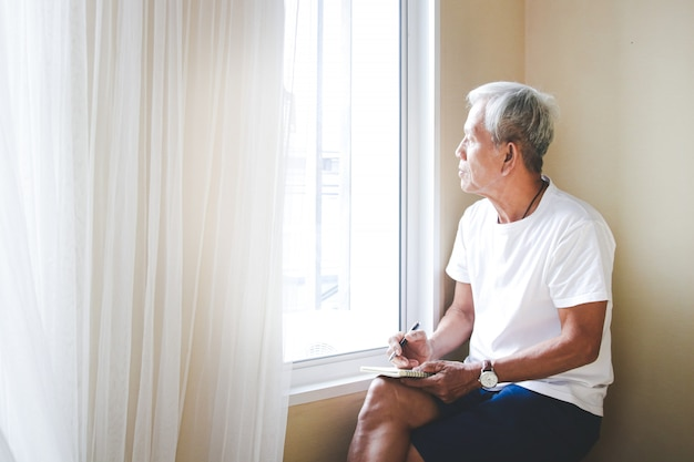 An elderly asian man sit down next to the window