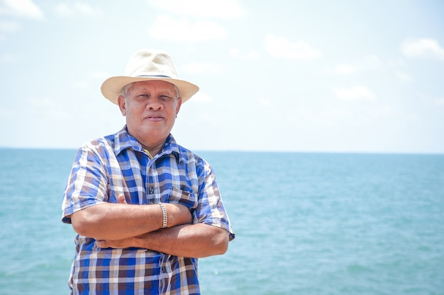An elderly asian man wearing a hat to visit the sea to relax