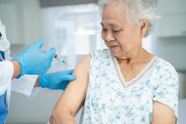 医師がコロナウイルスワクチンを接種するフェイスマスクを着用したアジアの高齢女性が注射を行う