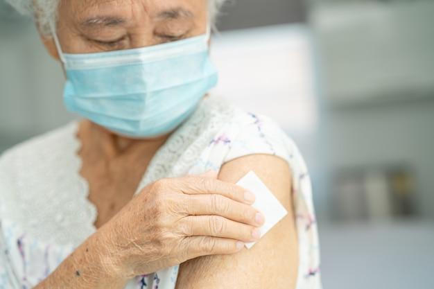 Elderly asian senior woman wearing face mask getting covid19 or coronavirus vaccine