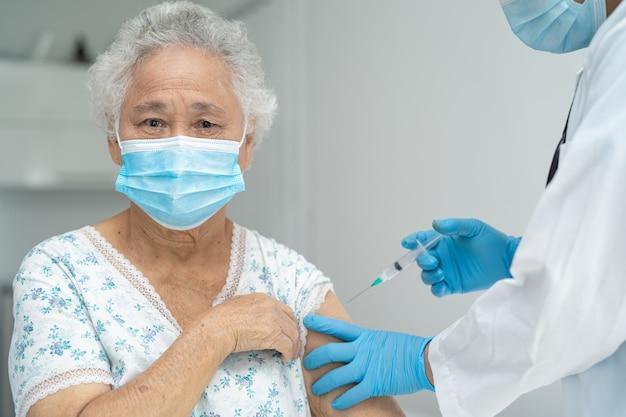 Covid19またはコロナウイルスワクチンを取得するフェイスマスクを身に着けている年配のアジアの年配の女性