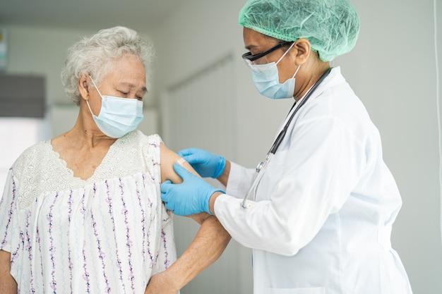 Covid19またはコロナウイルスワクチンを取得するフェイスマスクを身に着けているアジアの高齢の年配の女性