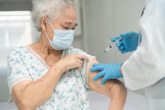 Covid19またはコロナウイルスワクチンを取得するフェイスマスクを身に着けている高齢のアジアの年配の女性