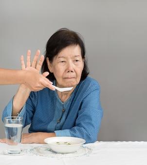Пожилой азиатской женщине скучно с едой
