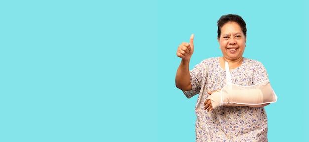 Пожилая азиатская женщина сломала руку, показывая два больших пальца над синей стеной