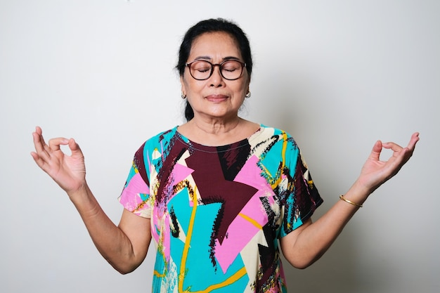 흰색 배경에 격리된 눈을 감고 명상 포즈를 취하는 아시아 노인 여성