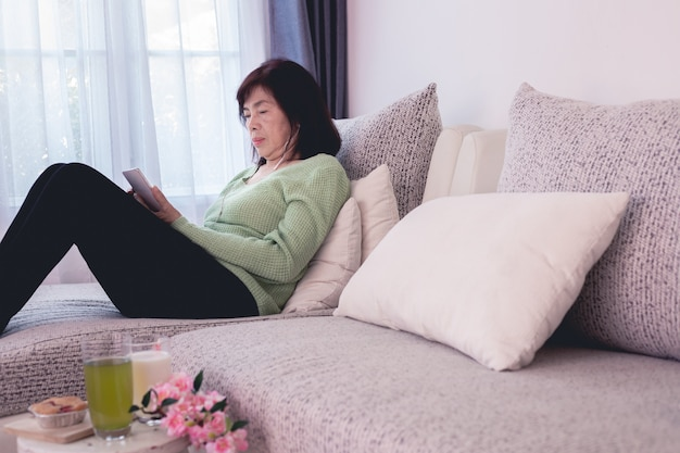 Elderly asian woman lying down on modern couch and using mobile phone with milk of glasses on table.