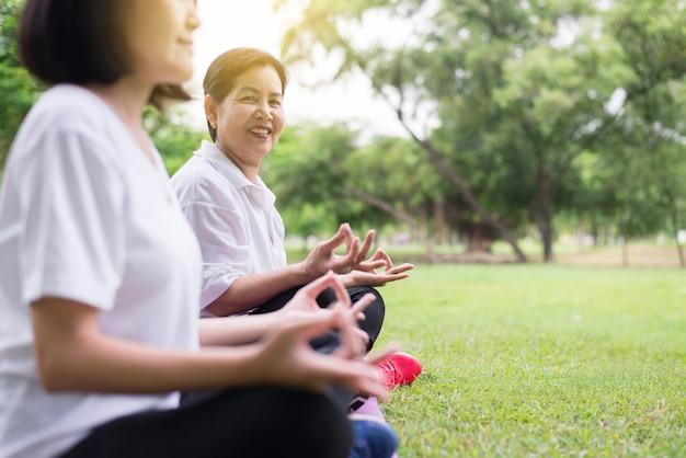 아침에 공원에 앉아 요가를 하는 나이든 아시아 여성, 행복하고 웃고, 긍정적인 생각, 건강 및 생활 방식 개념