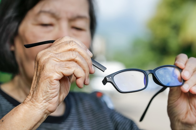 年配のアジアの女性は壊れた眼鏡を修理します