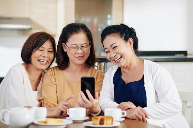 彼らが台所のテーブルに座っているときに彼女の友人にsmartpone画面で面白い写真を見せている年配のアジアの女性