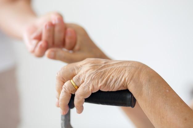 介護者と一緒に自宅で杖を使用してアジアの高齢女性が世話をします