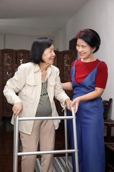 高齢者のアジアの女性が娘と一緒に家でウォーカーを使用して世話をする