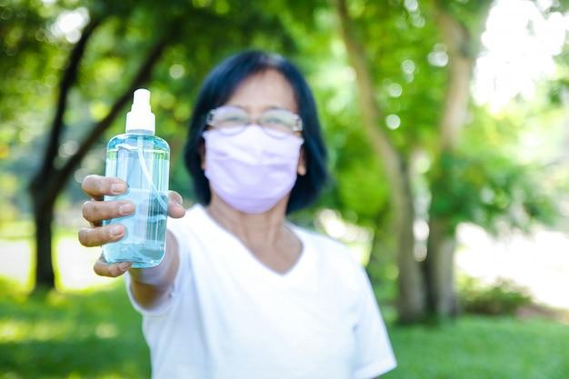 Пожилая азиатская женщина в маске и держит бутылку алкогольного геля