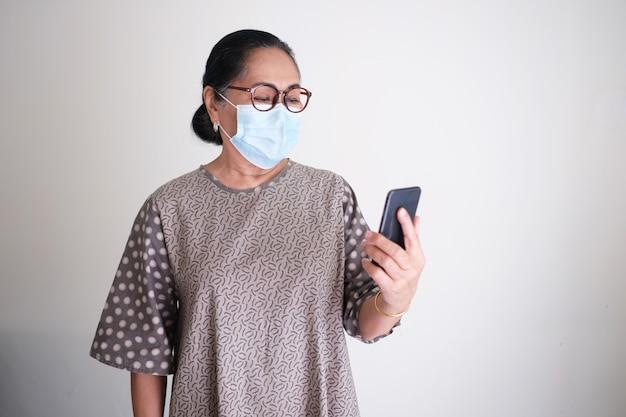 휴대 전화를 보면서 보호 의료 마스크를 쓴 아시아 노인 여성