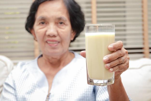 Elderly asian women drink milk containing calcium to prevent osteoporosis.
