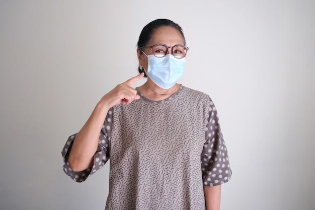 彼女が身に着けている彼女の保護医療マスクに指を指しているアジアの高齢女性