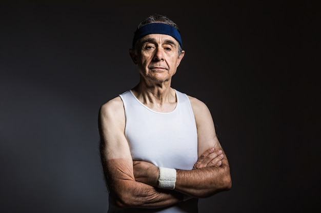 Пожилой спортсмен в белой рубашке без рукавов с солнечными отметинами на руках и синей повязке на голове со скрещенными руками на темном фоне. концепция спорта и победы.