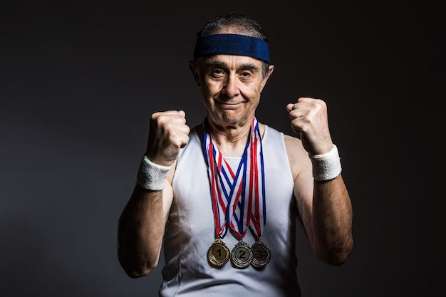 Elderly athlete wearing white sleeveless shirt, with sun marks on his arms, with three medals on his neck, clenching his fists, on a dark background. sports and victory concept.