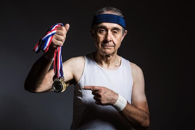 팔에 태양 표시가 있는 흰색 민소매 셔츠를 입은 노인 운동선수는 한 손에 메달 3개를 들고 어두운 배경에 있습니다. 스포츠와 승리 개념입니다.