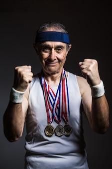 Пожилой спортсмен в белой рубашке без рукавов, с солнечными отметинами на руках, с тремя медалями на шее, сжав кулаки, на темном фоне. концепция спорта и победы.