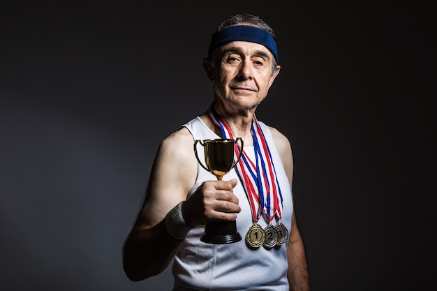 Пожилой спортсмен в белой рубашке без рукавов, с солнечными отметинами на руках, с тремя медалями на шее, с трофеем в руках, на темном фоне. концепция спорта и победы.