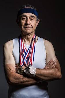 흰색 민소매 셔츠를 입은 노인 운동선수는 팔에 태양 표시가 있고 목에 메달 3개가 있고 팔짱을 끼고 어두운 배경에 있습니다. 스포츠와 승리 개념입니다.