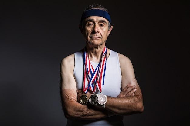 Пожилой спортсмен в белой рубашке без рукавов, с солнечными отметинами на руках, с тремя медалями на шее, со скрещенными руками, на темном фоне. концепция спорта и победы.
