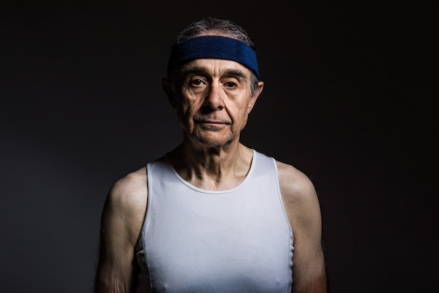 Пожилой спортсмен в белой рубашке без рукавов с солнечными отметинами на руках и синей повязке на голове на темном фоне. концепция спорта и победы.