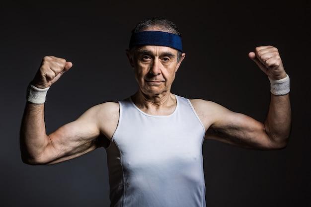 Пожилой спортсмен в белой рубашке без рукавов с солнечными отметинами на руках и синей повязке на голове, сжимающей бицепсы, на темном фоне. концепция спорта и победы.