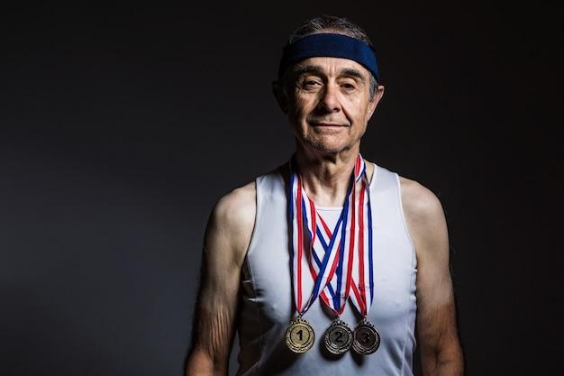 흰색 탱크톱을 입고 팔에 태양 표시가 있고 목에 3개의 메달이 있는 나이든 운동선수는 어두운 배경에서 그것을 보여줍니다. 스포츠와 승리 개념