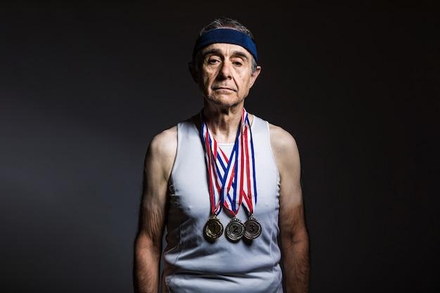Пожилой спортсмен в белой майке, с солнечными отметинами на руках, с тремя медалями на шее, демонстрирующими их, на темном фоне. концепция спорта и победы