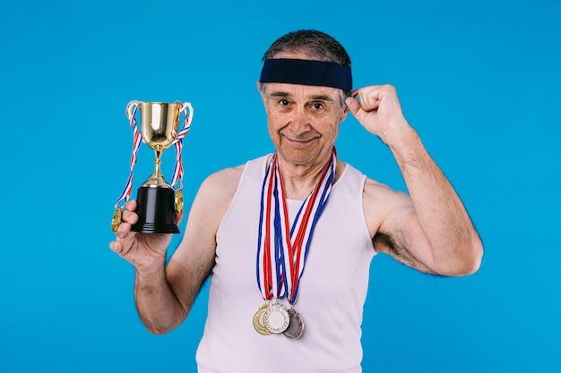 팔에 태양 표시가 있는 노인 운동선수, 목에 메달 3개, 손에 트로피, 힘의 표시로 주먹을 꽉 쥐고 파란색 배경