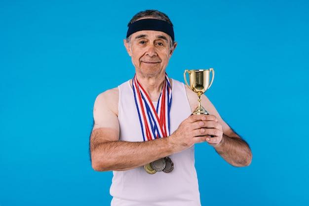 팔에 태양 표시가 있는 노인 운동선수, 목에 메달 3개, 손에 트로피, 파란색 배경