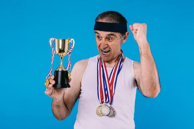 팔에 태양 표시가 있는 노인 운동선수, 목에는 메달 3개, 손에는 트로피가 있고, 비명을 지르며 파란색 배경에