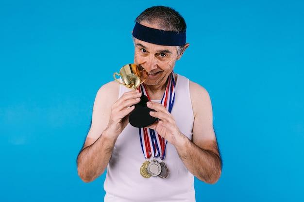 파란색 배경에 트로피를 물고 목에 3개의 메달이 있는 팔에 태양 표시가 있는 노인 운동선수