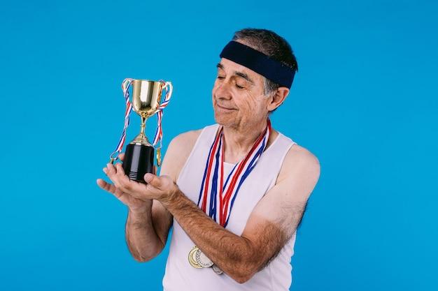 팔에 태양 표시가 있는 노인 운동선수, 목에 3개의 메달이 달린 리본이 달린 트로피를 파란색 배경에 보고 있습니다.