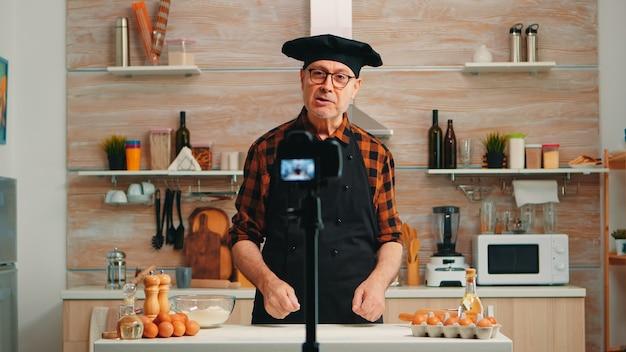キッチンでの料理レシピについてのビデオチュートリアルを録画する高齢者のパン屋。デジタル機器を使用してソーシャルメディアで通信、撮影、ブログを行うインターネット技術を使用する退職したブロガーchefinfluencer