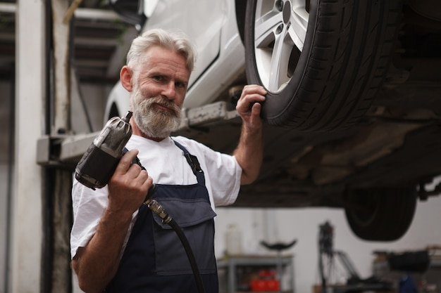 Пожилой бородатый работник автосервиса, держащий динамометрический ключ, стоит возле поднятого автомобиля, копировальное пространство