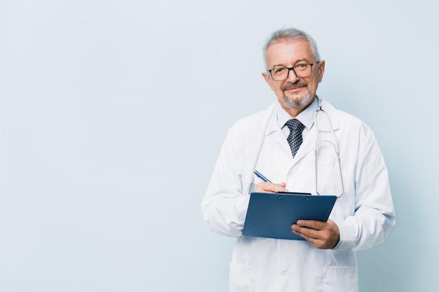 Пожилой бородатый мужской доктор в белой форме с стетоскоп с синей папки.