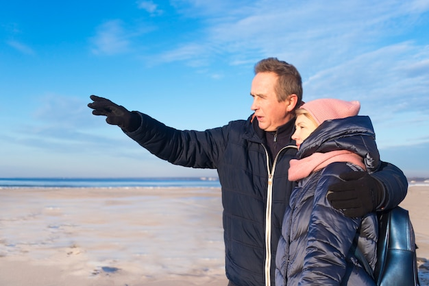 Elderly beautiful european senior retired couple in love walking on the beach, sea in a winter day in warm clothes. man hugs woman, wife, show, look, point to something in distance