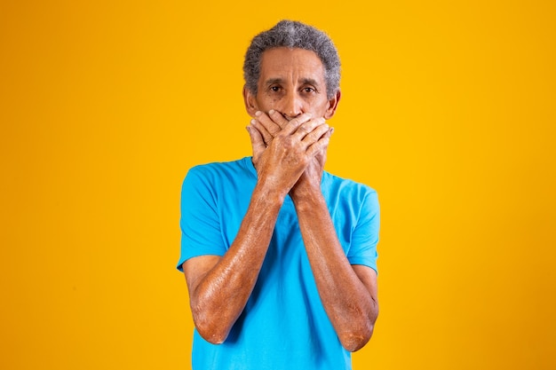 Elderly black man with hand over mouth in silence. racism concept