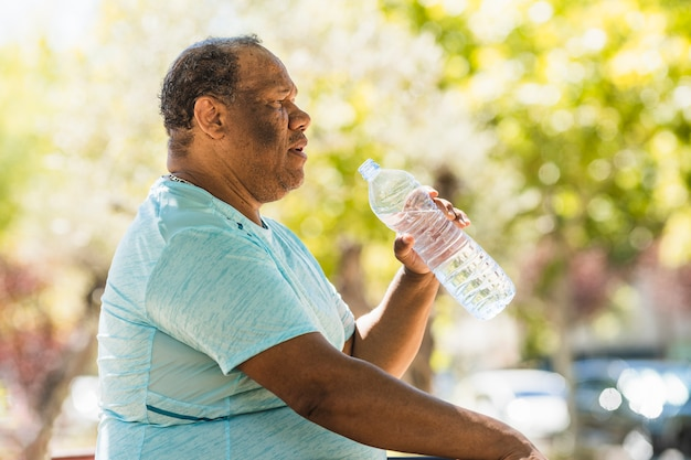 An elderly black man with overweight and morbid obesity is drinking water in the park