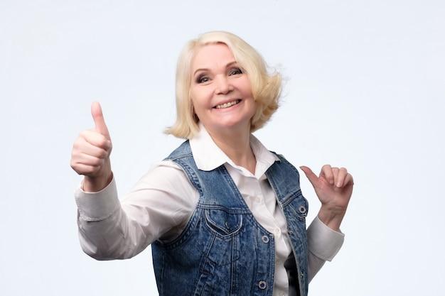 親指をあきらめて高齢者の金髪ヨーロッパの女性