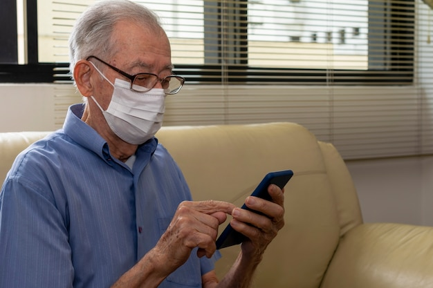 パンデミック時に携帯電話アプリケーションを使用して白い顔のマスクを持つブラジルの老人。家にいる。