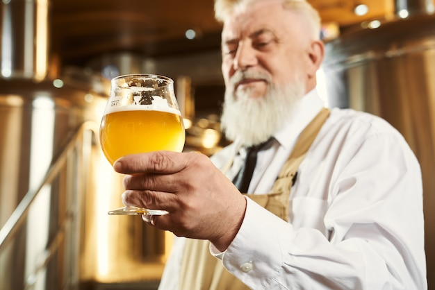 Elderly brewer holding glass with light beer